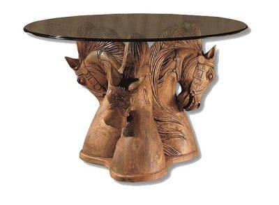 Mesa rústica redonda de cristal y madera con soporte tallado cabezas caballo